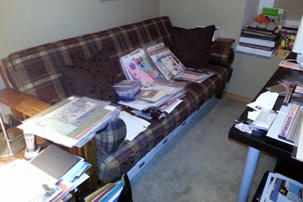 A futon covered with scrapbook supplies and layouts that need to be put away